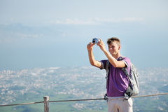 Young hiker with backpack making himself photo on the top of the mountain Vesuvius, Italy Stock Photography