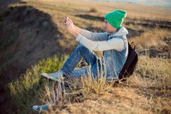Young hiker with backpack sitting on the mountain top while resting after active walk . Hiking in beautiful nature in sunny day, Royalty Free Stock Images