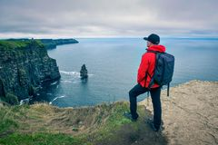 Young hiker standing at the cliffs of Moher Royalty Free Stock Photo
