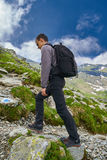 Young hiker with backpack on a trail Stock Images