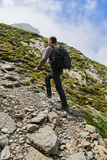 Young hiker with backpack on a trail. Young man with backpack hiking into the rocky mountains on a trail Stock Photos