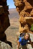 Young hiker climbs through rocks Stock Photography