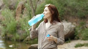 Young hiker drinking water at mountain valley stock footage