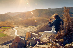 Young hiker enjoying sunset and taking picture royalty free stock photography
