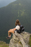 Young hiker girl rests on cliff and enjoys breathtaking scenery of mountains covered with pine forests Stock Photo