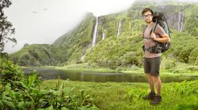 Hiker with backpack in front of a tropical waterfall Stock Photo