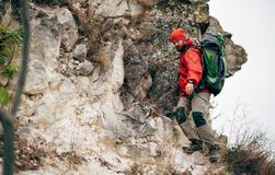 Young hiker male hiking in mountains wearing red clothes exploring new place. Traveler bearded man trekking and mountaineering. During his journey. Travel royalty free stock photography