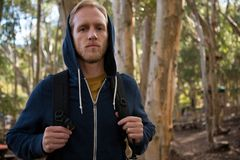 Young hiker man with backpack standing in the forest on a sunny day Royalty Free Stock Photos