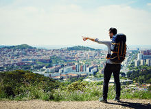 Young hiker man discovers a new city in his foot travel. Young hiker on the mountains stock photos