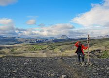 Young hiker man looking for a way next to Laugavegur signpost with stunning landscape view on background, Iceland royalty free stock photos