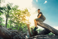 Young Hiker Man Resting On A Log In Summer Forest Royalty Free Stock Photography