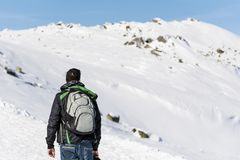 Young Hiker Man in the  Winter Mountain. Young man  standing near  winter mountain valley - adventure concept Royalty Free Stock Images