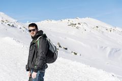 Young Hiker Man in the  Winter Mountain. Young man  standing near  winter mountain valley - adventure concept Stock Images