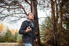 Young photographer photographing in autumn forest. Young hiker photographer photographing in autumn forest Royalty Free Stock Photo