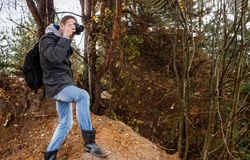 Young photographer photographing in autumn forest. Young hiker photographer photographing in autumn forest Stock Image