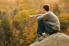 Young hiker relaxing on rock stock photography