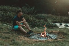 Young hiker sitting next to the fireplace and bonfire and thinking royalty free stock photos