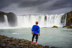 Hiker standing at the Godafoss waterfall in Iceland