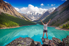 Young hiker standing with raised hands near the beautiful mounta Stock Image