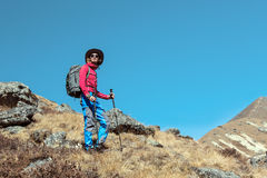 Young Hiker staying on grassy Mountain Slope Royalty Free Stock Images