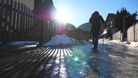 Young hiker with stick walks on ice trail at suburb. Unrecognizable guy with backpack goes on icy road during journey at