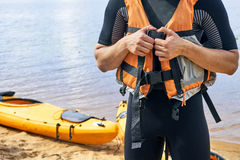 Young hiker wearing wetsuit putting on a life vest. Young hiker wearing wetsuit putting on a life jacket before sailing on kayak Royalty Free Stock Photo