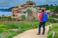 Young hiker woman with backpack enjoying the view, Ploumanach, France Stock Image