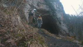 Young hikers in helmets coming out from the dark cave with flashlights