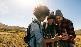 Young hikers looking at pictures on mobile phone Royalty Free Stock Photography