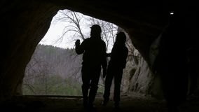 Young hikers silhouette in helmet enters from the forest to the dark cave with flashlight. Telephoto shot stock video