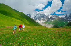Young hikers trekking in Svaneti. Georgia. Shkhara mountain in the background Stock Photo