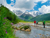 Young hikers trekking in Svaneti. Georgia. Shkhara mountain in the background Royalty Free Stock Photo