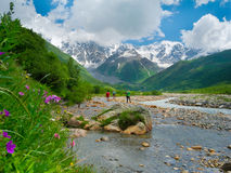 Young hikers trekking in Svaneti. Georgia. Shkhara mountain in the background Stock Photos
