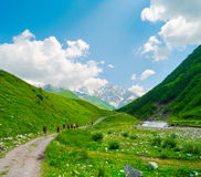 Young hikers trekking in Svaneti. Georgia. Shkhara mountain in the background Royalty Free Stock Images