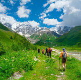 Young hikers trekking in Svaneti. Georgia. Shkhara mountain in the background Royalty Free Stock Image