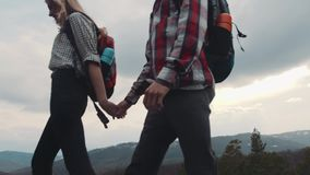 Young hikers wandering in the rocky mountains. Stylish couple. Love adventure, couple goals. Amazing nature, high hills. Slow motion, camera stabilizer shot stock video footage