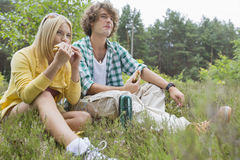 Young hiking couple eating sandwiches while relaxing in field Royalty Free Stock Photo