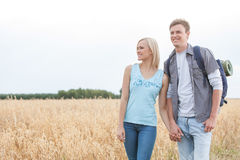 Young hiking couple holding hands while standing on field Royalty Free Stock Photo