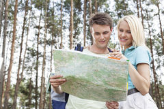 Young hiking couple reading map in forest Royalty Free Stock Photo