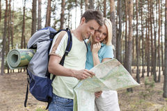Young hiking couple reading map in forest Stock Photos