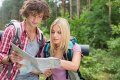 Young hiking couple reading map together in forest Stock Photo