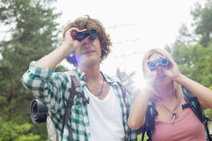 Young hiking couple using binoculars in forest Royalty Free Stock Photo