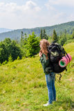 Young hiking woman standing on top of the mountain with valley on the background Royalty Free Stock Photo