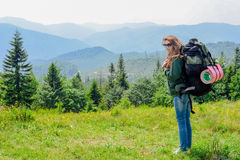 Young hiking woman standing on top of the mountain with valley on the background Stock Image
