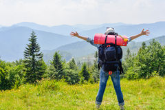Young hiking woman standing on top of the mountain with valley on the background. Happy young traveler with backpack Royalty Free Stock Photos