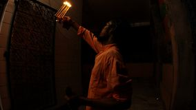 Young hindu monk rings bell and repeats movements with burning light fixture in front of enterance in temple night aarti dark even