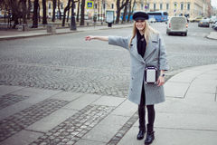 Young, hip and attractive blonde hailing taxi , girl in a stylish hat and a gray coat Royalty Free Stock Photography