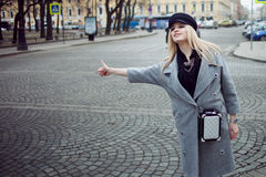 Young, hip and attractive blonde hailing taxi , girl in a stylish hat and a gray coat Stock Photos