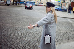 Young, hip and attractive blonde hailing taxi , girl in a stylish hat and a gray coat. Young, hip and attractive blonde walking around the city Royalty Free Stock Photos