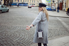 Young, hip and attractive blonde hailing taxi , girl in a stylish hat and a gray coat Royalty Free Stock Image